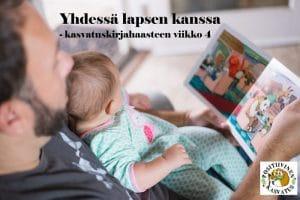 Lapsi isänsä sylissä lukevat kirjaa