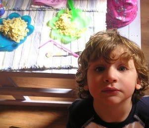 Lapsi ruokapöydän vieressä tuijottamassa ylös