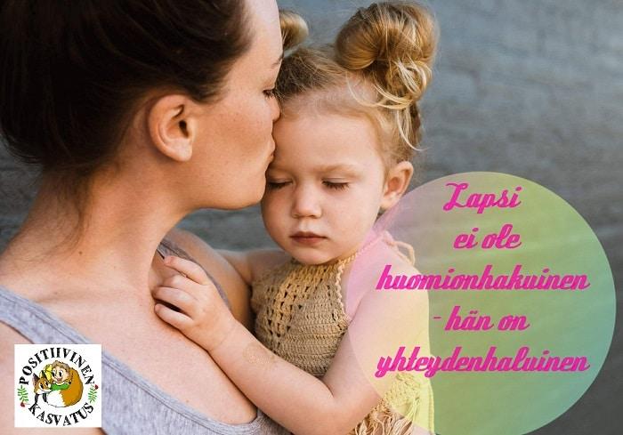 Äiti suukottaa otsalle sylissään olevaa lasta
