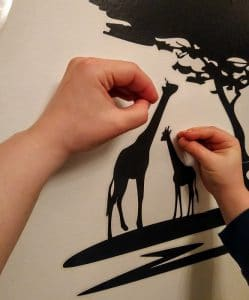 Lapsen ja aikuisen käsi sekä kirahvikuva
