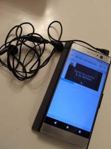 Kuvassa kännykkä ja kuulokkeet