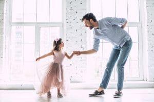 Isä kumartamassa lapselle pyytääkseen lasta tanssimaan