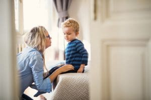 Aikuinen lapsen edessä polvillaan keskustelemassa