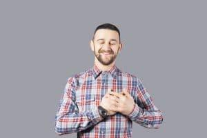 Mies pitää käsiä sydämellään